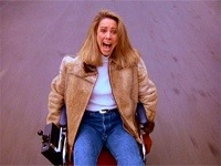 Blonde woman in wheelchair speeding down a hill with no breaks, in Seinfeld episode The Handicap Spot