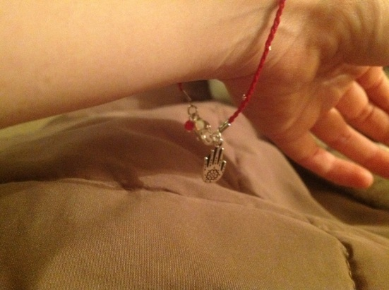 Red braided bracelet with silver beads and a hand charm.